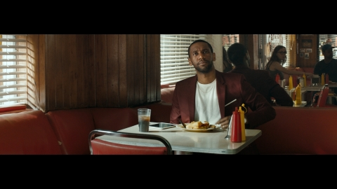 """""""The Look"""" follows a Black man throughout his day as he encounters a variety of 'looks' that symbolize a barrier to acceptance.  In this image you see his reaction as diners chose a far-away table after being directed to sit at a table near him. (Photo: Business Wire)"""