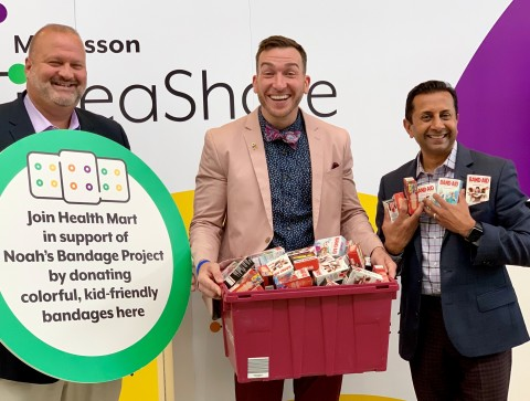 Health Mart's Chris Dimos and Nimesh Jhaveri hand over children's bandages to Paul Long of Noah's Bandage Project (pictured center). (Photo: Business Wire)