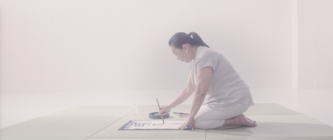 The scene where a mother turns toward a piece of calligraphy paper to write her daughter's name with a brush. Narration of the mother's voice explaining the origin of the daughter's name plays. (Photo: Business Wire)