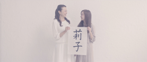A mother and daughter smile at each other as they hold up the paper with the daughter's name written in calligraphy. Viewers can tell from their expressions as they look at each other that they understood each other's feelings through the video letter. (Photo: Business Wire)