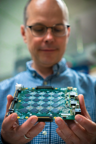 Rich Uhlig, managing director of Intel Labs, holds one of Intel's Nahuku boards, each of which contains 8 to 32 Intel Loihi neuromorphic chips. Intel's latest neuromorphic system, Pohoiki Beach, is made up of multiple Nahuku boards and contains 64 Loihi chips. Pohoiki Beach was introduced in July 2019. (Credit: Tim Herman/Intel Corporation)