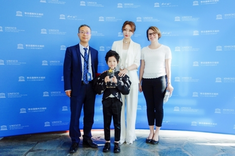 """Ms. Seasi Han, CEO of LONGINQUITY, and her cute son George Ding were invited to visit UNESCO on July 9, 2019. George Ding, the little gentleman, was honored as the """"UNITED NATIONS GOODWILL ANGEL."""" (Photo: Business Wire)"""