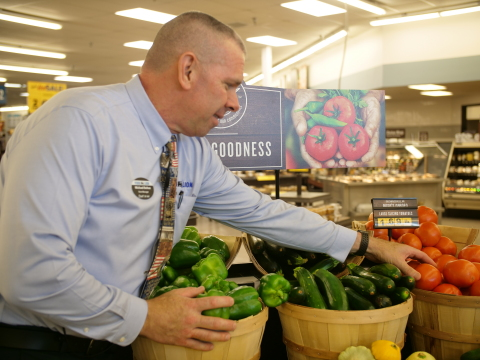 Food Lion store manager restocks local produce inside Timberville, Va., store (Photo: Business Wire)