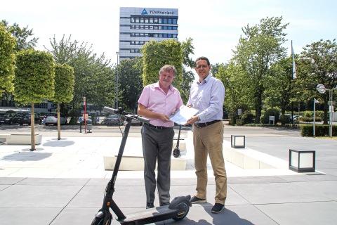 TÜV莱茵交通服务工程及型式认证全球副总裁Holger Hütz (左) 向赛格威-纳恩博欧洲、中东、非洲区总裁Dennis Hardholt交付两款电动滑板车的德国eKFV认证证书 (Photo: Business Wire)