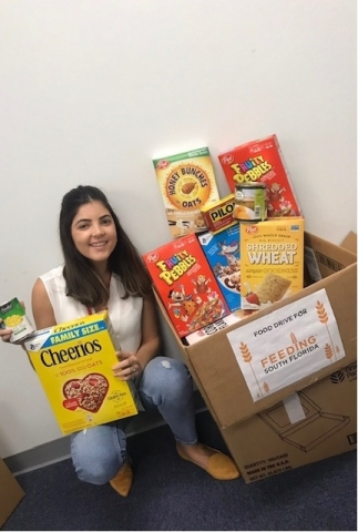 Melanie Da Silva shows some of the items donated by team members from PGT Innovations' Hialeah facility to Feeding South Florida in Pembroke Park, Florida (Photo: Business Wire)