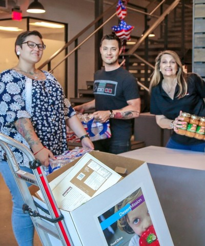 Jessica Craft, David Slater and Leanne Harter from PGT Innovations' Phoenix facility help load items collected from their location to be delivered to Desert Mission Food Bank in Phoenix, Arizona. (Photo: Business Wire)