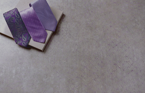 Wilsonart's Purple Construct is a large-scale design with a concrete grey background with a distressed geometric overlaid pattern. (Photo: Wilsonart LLC)