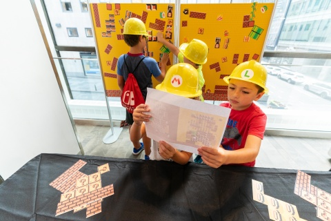 In this photo provided by Nintendo of America, siblings Gavin, age 9, Glen, age 7, and Grace, age 5, with Maximo J., age 7, participate in a Super Mario Maker 2 Puzzle Challenge during a special event at the Nintendo NY store in Rockefeller Plaza on Aug. 18, 2019. Super Mario Maker 2 is now available for the Nintendo Switch system. (Photo: Business Wire)