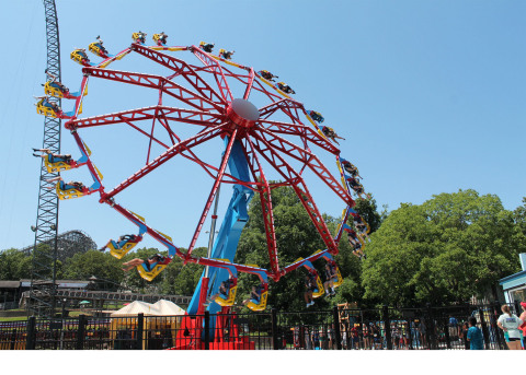 (Image) Riders board an open-air seat with feet dangling below on Catwoman Whip. As the giant wheel begins to whip around horizontally, the entire ride lifts to heights reaching 67 feet into the air and tilt to a vertical position, rotating round and round at a high speed. (Photo: Six Flags)