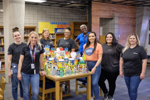 Desert Financial Credit Union employees pose for a photo with some of the supplies donated for the back-to-school drive. (Photo: Business Wire)