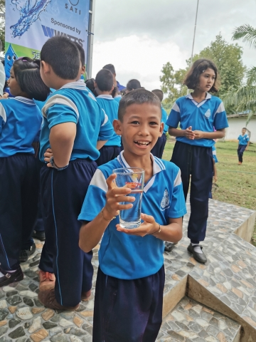 A child from the Sa Kaeo province in Thailand enjoys a glass of water after Watts and Planet Water Foundation built a water filtration tower that provides 1,000 people with 10,000 liters of clean water per unit daily. (Photo: Business Wire)
