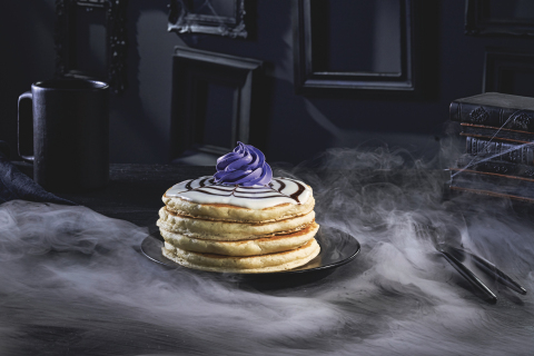 Wednesday's Web-Cakes, the centerpiece of the Addams Family menu at IHOP, are made with a stack of fluffy, signature Buttermilk pancakes topped with cupcake icing, webbed with HERSHEY'S chocolate syrup and finished with violet whipped topping. (Photo: Business Wire)