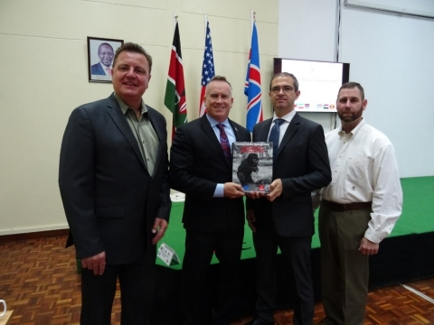 Caliburn presents a copy of one of 12 U.S.-developed training manuals to Larry Swift (U.S. Department of State) and Alexander Riebl (UNMAS). Pictured from left to right: Phillip Ayrton, Munitions and Environmental Remediation Project Manager (Caliburn); Larry Swift, Training Program Manager (contractor with U.S. Department of State); Alex Riebel, IED Threat Mitigation Advisor (UNMAS); David Courtney, Munitions and Environmental Remediation International Operations Program Manager (Caliburn). (Photo: Business Wire)