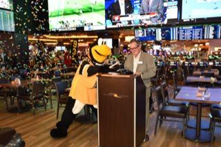 """Bill Keena, general manager of Rivers Casino Pittsburgh, and """"Iceburgh,"""" Pittsburgh Penguins mascot, celebrate the grand opening of BetRivers Sportsbook. (Photo: Business Wire)"""