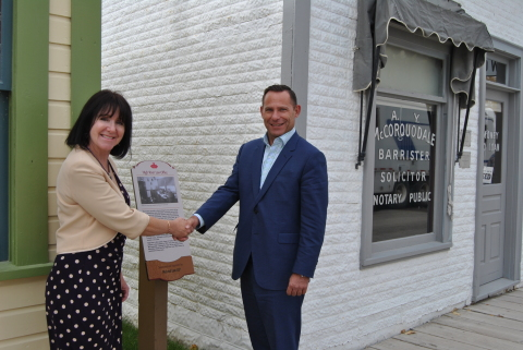 Laurene Mitchell of Heritage Park and Robin Lokhorst, Managing Partner of McLeod Law shake hands in front of the High River Law Office. (Photo: Business Wire)