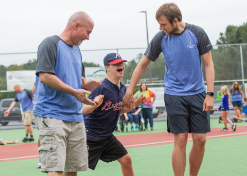 Ascend Cares volunteers help a Miracle League player round the bases on their new field. (Photo: Business Wire)