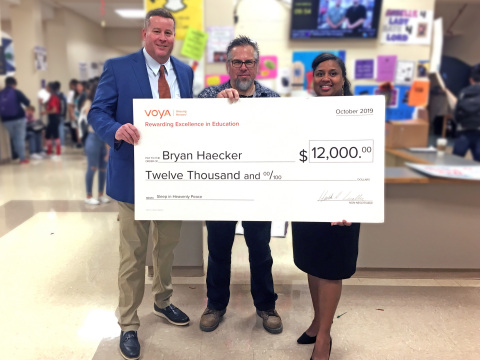 San Antonio, Texas teacher Bryan Haecker from Earl Warren H.S. (pictured in middle) is awarded a grant for $12,000 as the second place winner of Voya's Unsung Heroes program. David Bowman, regional vice president, Voya Financial (pictured on left) presented the check to Mr. Haecker, alongside Valerie Sisk, principal of Earl Warren H.S. (pictured on right).