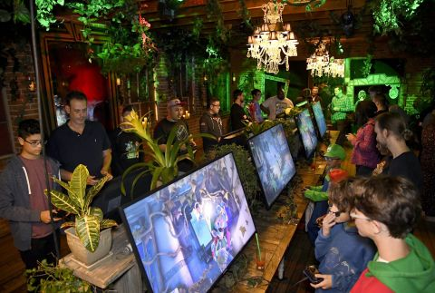 In this photo provided by Nintendo of America, fans enjoy a demo of the Luigi's Mansion 3 game at a preview event on Oct. 18 in Los Angeles, surrounded by a lush garden inspired by a level in the game. Luigi's Mansion 3 is the latest game in the Luigi's Mansion franchise, with Luigi returning as the reluctant and cowardly hero, tasked with saving his friends from a spooky hotel. The game launches exclusively for the Nintendo Switch system on Oct. 31.