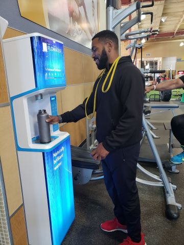 24 Hour Fitness Member Using a FloWater Refill Station (Photo: Business Wire)
