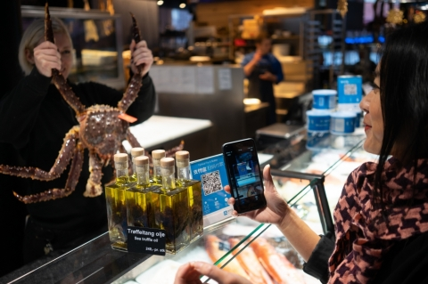A Chinese tourist uses Alipay to pay for items at a store in Norway. (Photo: Business Wire)