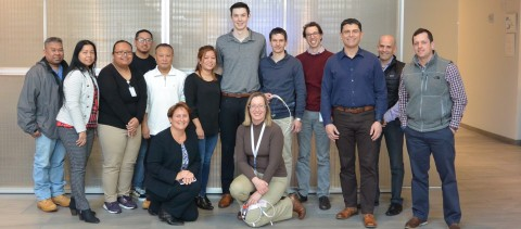 Adam Millar (center, wearing gray shirt) is pictured with Abiomed employees who helped make his Impella heart pumps. Adam was 18 when he received an Impella CP and RP. Initially, physicians considered Adam a candidate for a costly implantable LVAD and heart transplant, but they were not needed after Impella helped recover his native heart. (Photo: Business Wire)