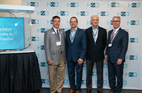 HZO and Government Leaders at the Open House, pictured next to a fully submerged LED display, protected by HZO's waterproofing technology . From Left: TJ Cawley, Mayor of Morrisville, North Carolina, Stephen Gold, HZO Chief Commercial Officer, Bill McCombe, HZO Chief Financial Officer, and John Hardin, Executive Director of the Office of Science, Technology & Innovation in the North Carolina Department of Commerce (Photo: Business Wire)