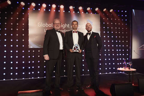 Genesee & Wyoming UK/Europe Region Intermodal Commercial Director Clive Slayford (center) accepts Freightliner's award for Rail Freight Operator of the Year at the 2019 Global Freight Awards, flanked by Peter Livey (left), MD of category sponsors HMM, and comedian Tom Allen, host (right). (Photo: Business Wire)