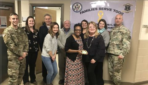 Corvias employees, pictured here, present the Rhode Island National Guard with gift cards to purchase food for this Thanksgiving holiday. (Photo: Business Wire)