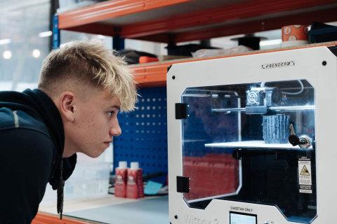 14歳のHarris Gribbleくんが3Dプリンターで製造されているオープン・バイオニクスのヒーロー・アームを観察(写真:ビジネスワイヤ)