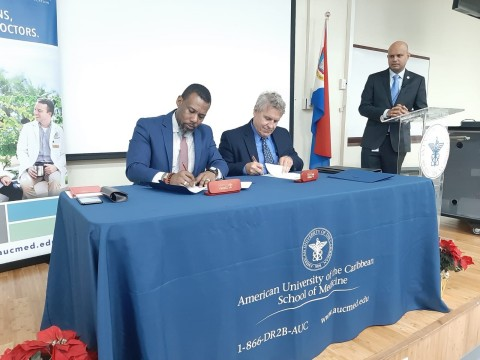 Ronald Jackson, CDEMA Executive Director and Dr. Mark Quirk, Executive Director of the Caribbean Center for Disaster Medicine and Senior Associate Dean for Medical Education at AUC School of Medicine, sign an agreement to increase collaboration while Hazarie Ramoutar, Senior Administrator for Campus Operations at AUC School of Medicine, looks on. (Photo: Business Wire)