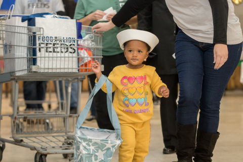 "A child of a servicemember receives donated groceries from Food Lion at one of the grocer's recent ""Season of Caring"" events in Newport News, Va. (Photo: Business Wire)"
