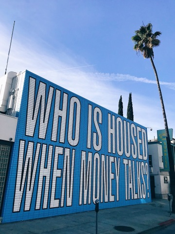 """Internationally renowned conceptual artist Barbara Kruger distilled the essence of the housing crisis in the U.S. in a new word text mural: """"WHO IS HOUSED WHEN MONEY TALKS?"""" created pro bono for the advocacy group Housing is a Human Right. The mural is on Sunset Blvd. in a rapidly gentrifying section of Hollywood, California."""