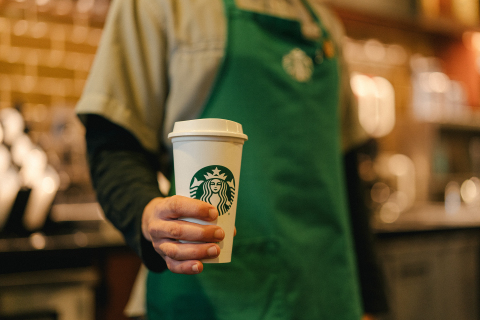 A Starbucks barista hands a reusable cup to a customer. As part of the company's new sustainability commitments, the company is working to encourage more use of reusable cups. (Photo: Business Wire)