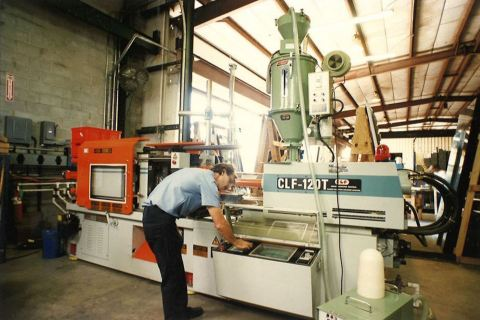 Team member operates one of the company's first injection molding machines to produce parts for the Progressive Glass Technology division of VinylTech, which was launched in 1987. (Photo: Business Wire)