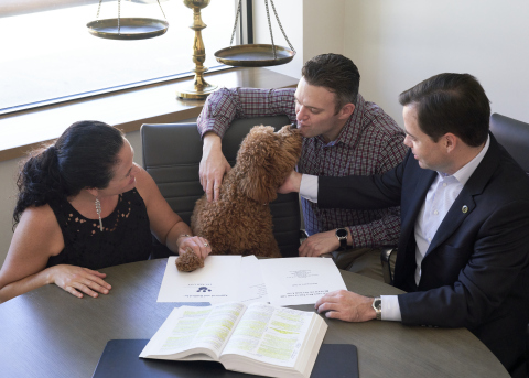 Golden doodle dubbed as @TuckerinPhilly shows his affection to parents after attorney Robin Merriman finalizes pet trust. (Photo: Business Wire)