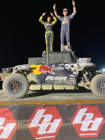 Kurtis Elliot (left) and Mitch Guthrie Jr. (right) standing atop the 2019 Turbo S of Mitch Guthrie Jr. on the podium after winning the 2020 Baja Designs UTV Night Race at the King Shocks Laughlin Desert Classic. (Photo: Best In The Desert)