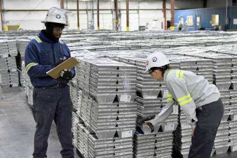 American Zinc Recycling employees pictured in front of pallet of SHG zinc ingots at Rutherford County facility. (Credit: American Zinc Recycling)