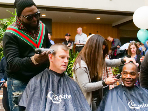 """David """"Big Papi"""" Ortiz, former Major League Baseball designated hitter and first baseman for the Boston Red Sox, shaves the head of Sam Kennedy, President and CEO of the Boston Red Sox, during Granite's 7th Annual """"Saving By Shaving"""" fundraising event to benefit Boston Children's Hospital. (Photo: Business Wire)"""