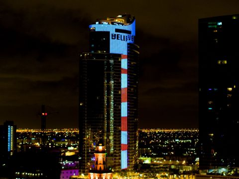 """Paramount Miami Worldcenter tower where musician """"Pitbull"""" debuts new global anthem, entitled, """"I Believe That We Will Win."""" The song is broadcast at start of nightly stars and stripes 10 PM curfew tower lighting at new 700-foot, $600-million skyscraper, which features world's most-advanced L.E.D. animation system displaying 60-story tall electronic American flag and 100-yard long ticker-tape style read-out of song lyric, """"Believe."""" (Bryan Glazer 