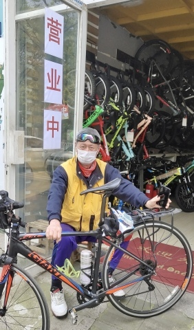 """""""We're open"""" says the bright red sign behind Wuhan bicycle store owner Mr. Fang Qianjin, signaling that the city is ready to ride again after a two-month lockdown. (Photo: Business Wire)"""