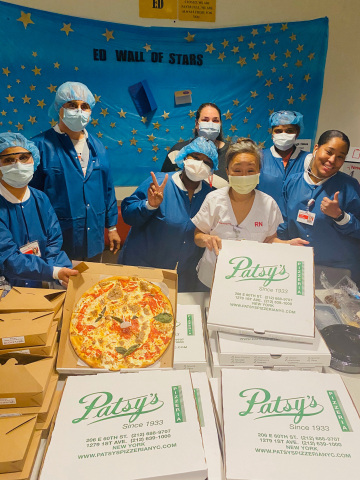 """Pictured: The Emergency Room Staff at NY Presbyterian Weil Cornell Medical Center in NYC, eating Patsy's Pizza that was donated by TSR Inc.'s """"Feed The Heroes"""" program. (photo cred - Cora Yi)"""