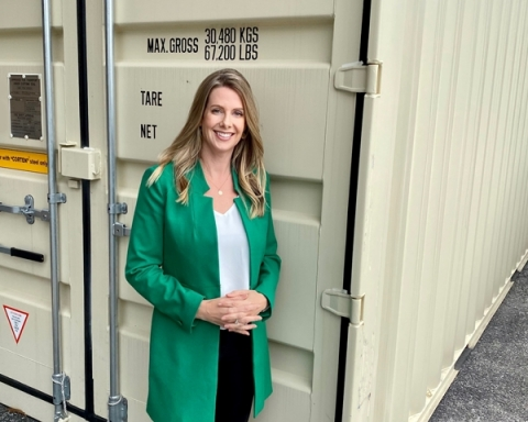 Amy Thompson, President & co-Founder of Northern Container Sales, stands in front of a shipping container. (Photo: Business Wire)