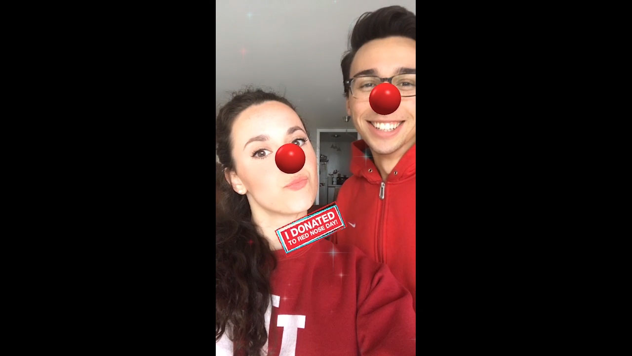 Girl and guy smile for selfie with Red Noses on social media after donating to Red Nose Day at Walgreens.com/RedNoseDay