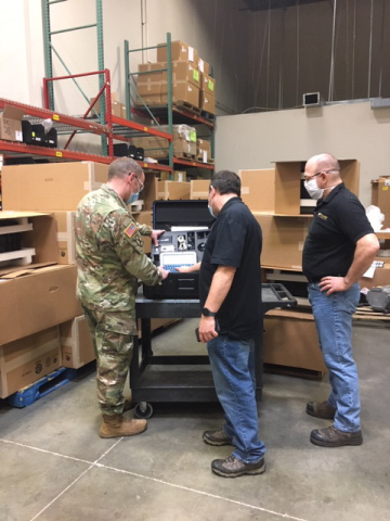 Captain Adam Hever of Army National Guard Bureau (NGB) Headquarters, Savi Technology's Doug Schreffler and Chris Macek of First Source Electronics (FSE), a division of Commercial Vehicle Group, Inc., inspect order of 221 Savi Portable Deployment Kit (PDK) III units at FSE's Maryland location. (Photo: Business Wire)