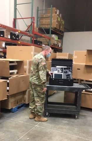 Captain Adam Hever of Army National Guard Bureau (NGB) Headquarters inspects a Savi Portable Deployment Kit (PDK) III at Maryland location of First Source Electronics, a division of Commercial Vehicle Group, Inc.  (Photo: Business Wire)