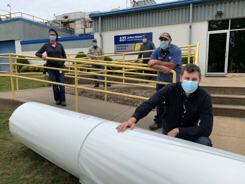 Johns Manville employees in Spartanburg, South Carolina, pose beside the nonwoven fabric that will be used for manufacturing of urgently needed disposable medical gowns used in the fight against the spread of COVID-19. (Photo: Business Wire)
