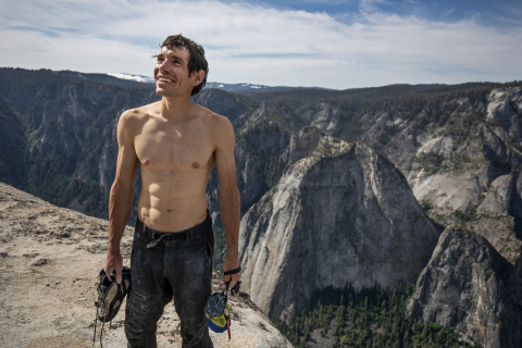 Alex Honnold holds all of his climbing gear atop the summit of El Capitan. He just became the first person to climb El Capitan without a rope. (Credit: National Geographic/Jimmy Chin)