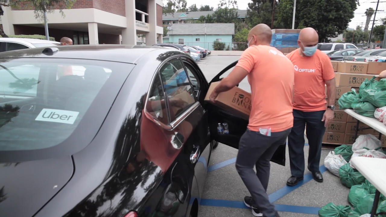 B ROLL - Volunteers Loading Food Boxes into Uber Vehicles for Delivery