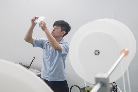 """On April 30, a technician in Wugu District, New Taipei City, inspects a sample at Chang Hong Machinery, one of several local manufacturers that form Taiwan's """"national team"""" responsible for building production lines and increasing the country's mask output to 20 million pieces per day. (By Lin Chun-yao, CNA)"""