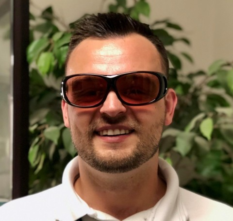 UC Davis Eye Center color blind study participant Alex Zbylut wearing EnChroma glasses for color blindness (Photo: Business Wire)